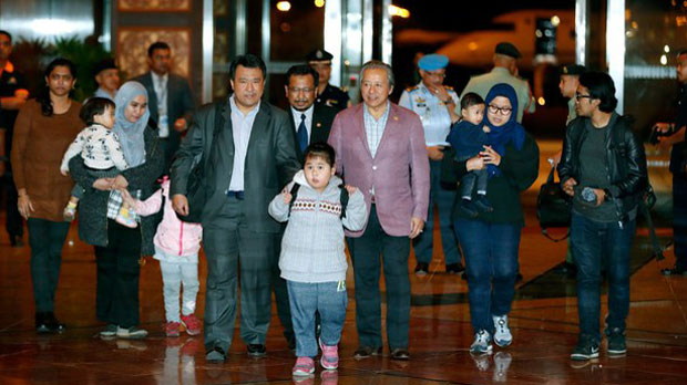 Malaysians who were stranded in Pyongyang, North Korea, walk with Foreign Minister Anifah Aman (center right), after arriving at Kuala Lumpur International Airport in Sepang, Malaysia, March 31, 2017.