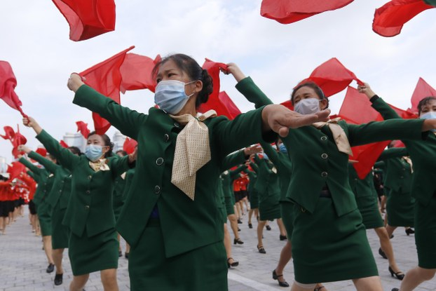 Women wearing face masks to help curb the spread of the coronavirus parade with flags during a rally to welcome the 8th Congress of the Workers' Party of Korea at Kim Il Sung Square in Pyongyang, North Korea, Monday, Oct. 12, 2020.