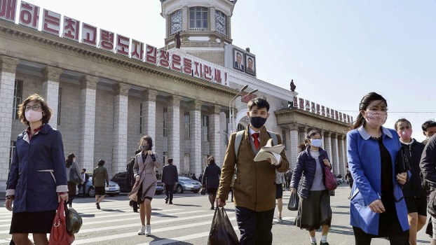 People wearing protective face masks walk amid concerns over the coronavirus in front of Pyongyang Station in Pyongyang, April 27, 2020.