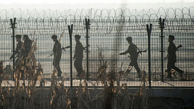 North Korean soldiers patrol a fence line near the town of Sinuiju, Feb. 10, 2016.
