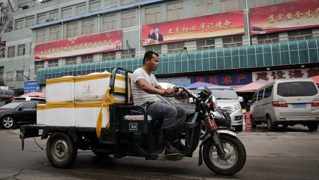A man rides a motor-tricycle loaded with seafood products past by a billboard featuring Chinese President Xi Jinping and the government propaganda on display at the Jingshen seafood market in Beijing, Thursday, July 12, 2018.