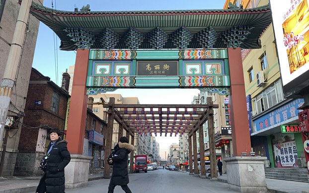 """Pedestrians walk by the entrance of """"Koryo street"""", a commercial area that used to house many businesses engaged in trade with North Korea, in the Chinese city of Dandong bordering North Korea in northeastern China's Liaoning Province, Saturday, Feb. 23, 2019."""