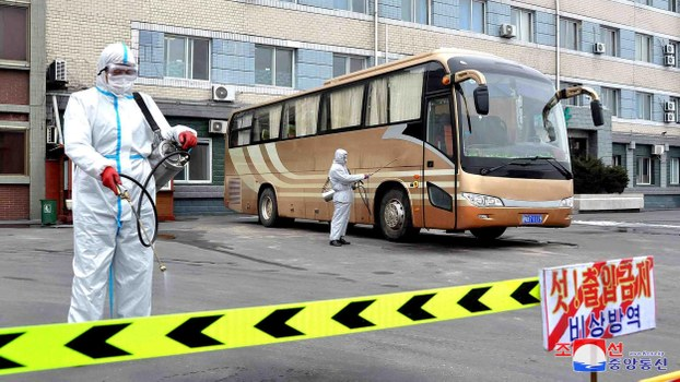 This undated picture released from North Korea's official Korean Central News Agency (KCNA) on March 4, 2020 shows workers disinfecting a bus and parking lots to prevent the spread of the COVID-19 coronavirus in Sinuiju, North Pyongan Province.
