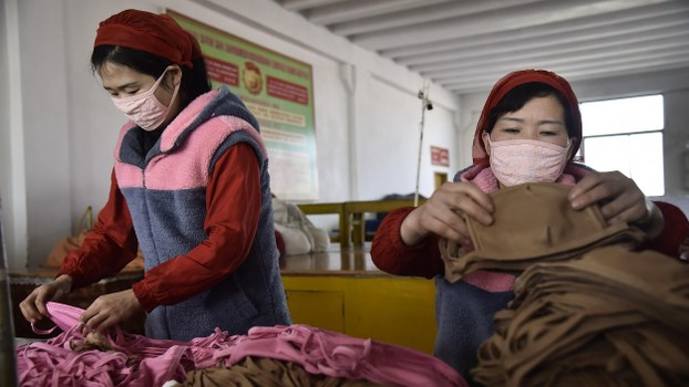 Workers at the Songyo Knitwear Factory in Pyongyang, North Korea produce masks for protection against COVID-19 on February 6, 2020.