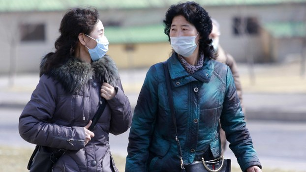 People wear masks to protect from a new coronavirus as they walk through the Kwangbok Street in Pyongyang, North Korea Wednesday, Feb. 26, 2020.