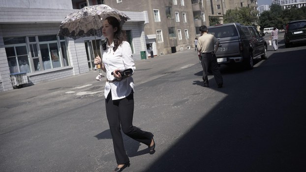 A woman walks with her purse and parasol past department stores in Pyongyang, North Korea in a file photo.