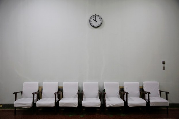 A clock hangs above chairs inside a waiting room at a hospital during a government organised visit for foreign reporters in Pyongyang in a file photo.