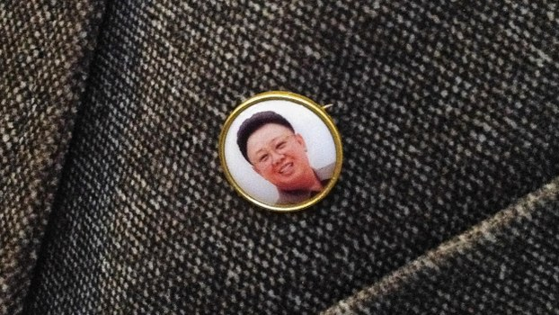 In this February 25, 2013 photo a pin depicting the image of the late Kim Jong Il is seen on the jacket of a North Korean man in Pyongyang, North Korea. A new version of the pin with a red background has been distributed among the country's elite since June 2019.