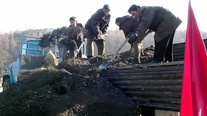 Workers shovel manure at a cooperative farm in Kaesong, North Korea.