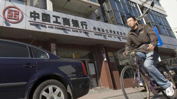 A man rides past a branch of the Industrial and Commercial Bank of China in the border city of Dandong in northeast China, Friday, in a file photo.