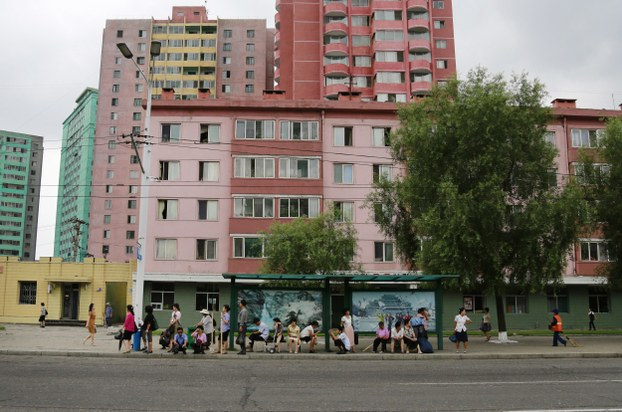 People wait for public transport as colorful apartment buildings are seen in the background in Pyongyang, North Korea, Wednesday, July 25, 2018.