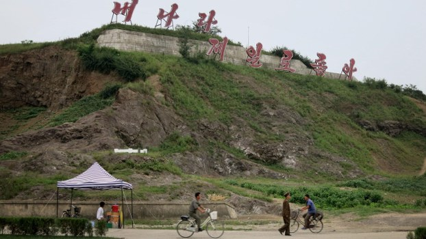 "This file photo shows a roadside kiosk and passers-by below a sign saying ""My country is the best"" on the main road into Sinuiju, a North Korean city on the border with China"