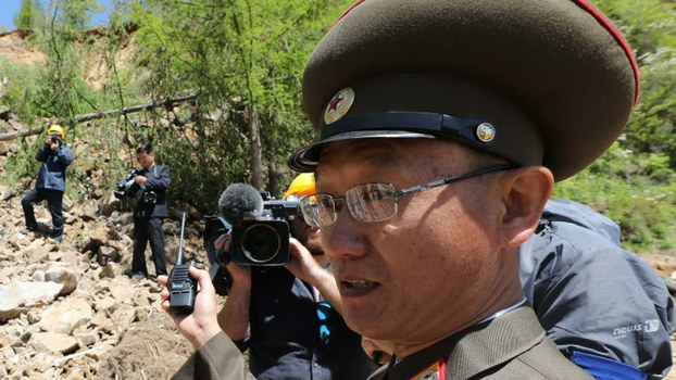 A bespectacled North Korean People's Army (KPA) soldier inspects debris following a demolition ceremony at North Korea's Punggye-ri nuclear test facility, May 24, 2018.
