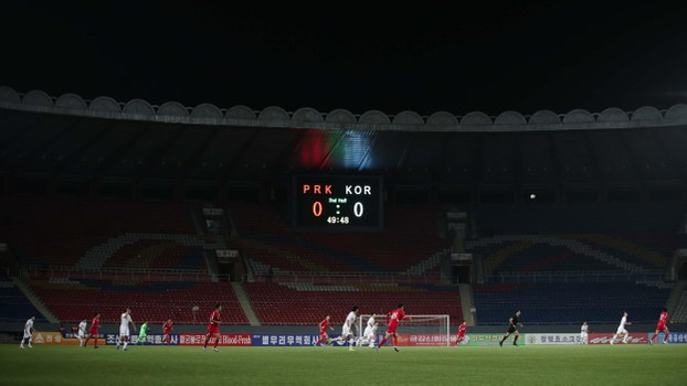 In this handout photo taken on October 15, 2019 by the Korea Football Association (KFA) South Korean (white) and North Korean (red) players fight for the ball during a qualifier match for the 2022 FIFA Men's World Cup at an empty Kim Il Sung Stadium in Pyongyang.