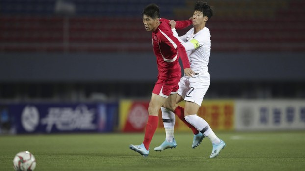This handout photo taken on October 15, 2019 by the Korea Football Association (KFA) shows South Korea's Son Heung-min (R) and North Korea's Ri Yong-chol (L) fighting for the ball during the Men's World Cup 2022 Qualifying Asian zone Group H football match between South Korea and North Korea at Kim Il Sung Stadium in Pyongyang.