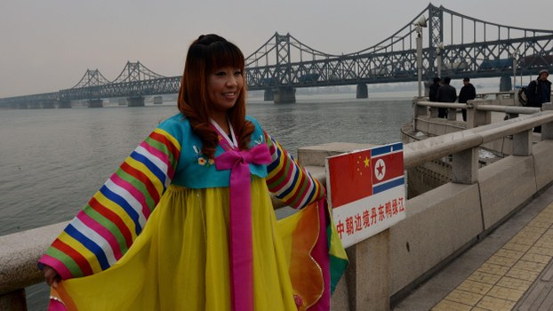 A Chinese woman poses in Korean clothing as trucks carrying Chinese-made goods cross into North Korea on the Sino-Korean Friendship Bridge at the Chinese border town of Dandong in a file photo.