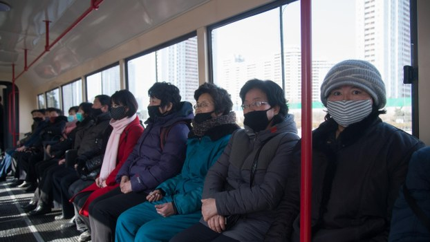 Commuters wearing face masks ride a tramcar in Pyongyang on February 26, 2020.