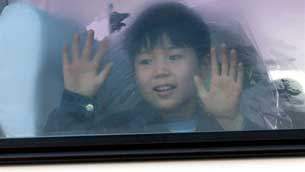 A young North Korean defector waves from a bus on its way to Seoul, Mar. 18, 2002.