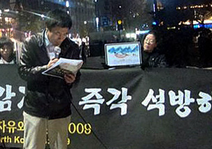 Robert Park reads a statement about North Korean human rights in the streets of Seoul, South Korea, on December 9th.