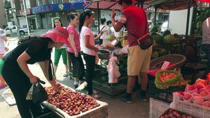 North Korean women from the Hong Chao Zhi Yi garment factory ask for the price of fruit at a street market in the city of Hunchun, in China's Jilin province, Sept. 2, 2017.