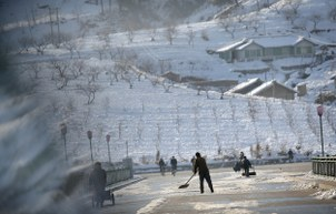 North Korean men clear ice and shovel snow off a road on in Hyangsan county, North Pyongan province, North Korea in a file photo.