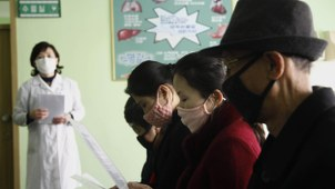 People review information explaining the COVID-19 coronavirus at the Phyongchon District People's Hospital in Pyongyang, North Korea, Wednesday, April, 1, 2020.