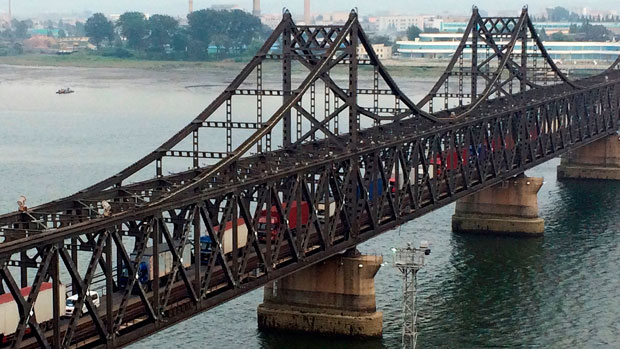Trucks move along a bridge connecting North Korea with China near the port city of Dandong in a Sept. 4, 2017 photo.