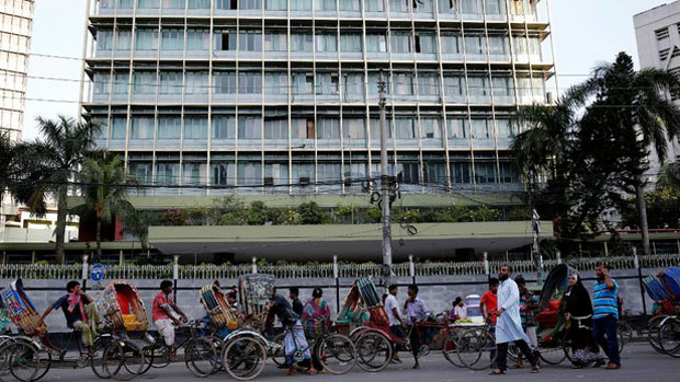 Commuters walk past the headquarters of Bangladesh's central bank in Dhaka in a file photo.