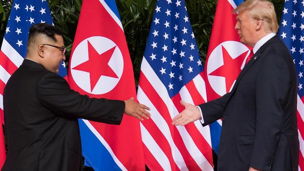 US President Donald Trump (R) shakes hands with North Korea's leader Kim Jong Un (L) at the start of their historic US-North Korea summit, at the Capella Hotel on Sentosa island in Singapore, June 12, 2018.