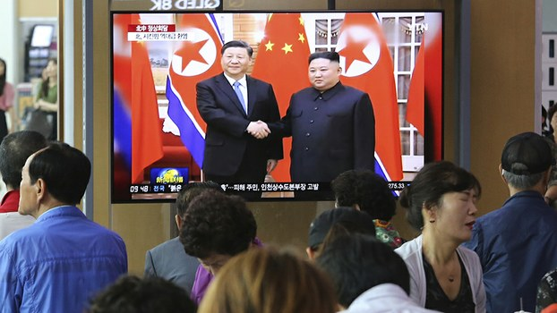 People in Seoul, South Korea watch a TV screen showing North Korean leader Kim Jong Un, right, alongside Chinese President Xi Jinping, during Xi's two-day visit to North Korea, June 21, 2019.