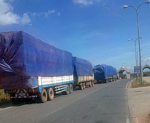 Lao trucks loaded with logs wait at the Lao Bao-Dansavanh international border checkpoint in Savannakhet province en route to Vietnam, Dec. 15, 2015.