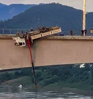 A crane truck carrying construction materials was found flipped over at the end of a rail bridge under construction over the Mekong River in Luang Prabang province, Laos, Sept. 15, 2020.