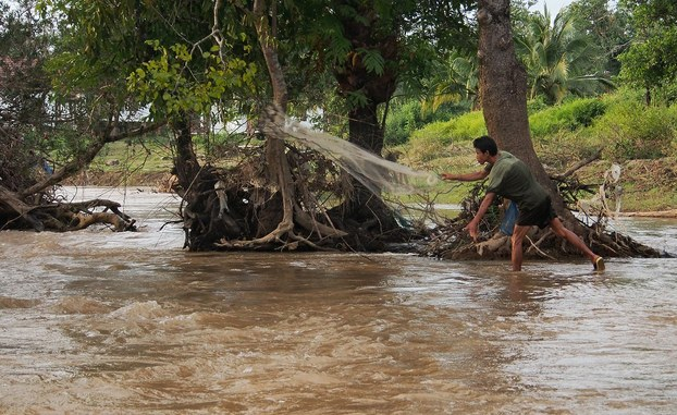 A fisherman casts his net in the Hou Sahong channel in a file photo.
