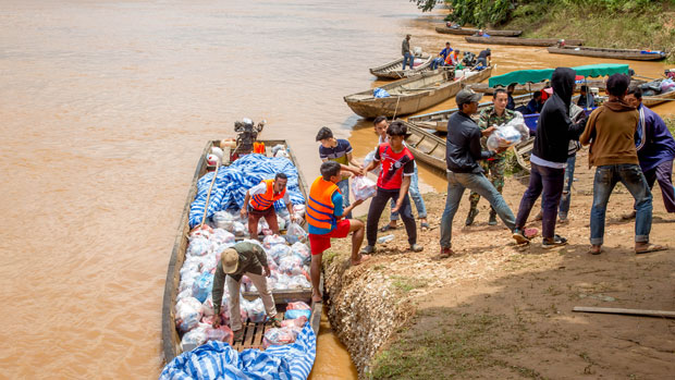 Volunteers unload food and other supplies for victims of a flood caused by a hydro power dam burst to a relief station at Sanamxay in southern Laos' Attapeu Province, Aug. 1, 2018.