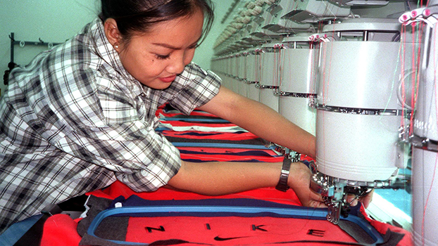 A file photo shows a female worker embroidering logos on Nike apparel in a privately owned garment factory in Vientiane.