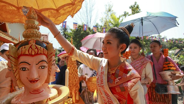 "Nang Sangkhan, or Miss Lao New Year, pours water mixed with frangipanis and perfume over the head of a statue as she takes part in ""Pi Mai Lao,"" or Lao New Year celebrations in Vientiane in a file photo."