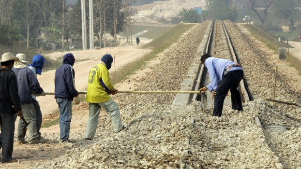 In a file photo, construction workers rake gravel  on the new railroad tracks across the Thai_Lao Friendship bridge in Thanalaeng, Laos.