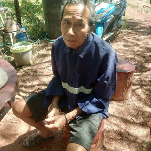 In this file photo taken in October 2019, an elderly Lao landowner, Thitphay Thammavong, is handcuffed in Bolikhamsai province's Pakkading district.