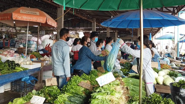 This March 25, 2020 photo shows a local market in Laos where patrons and workers wear masks to prevent the spread of the coronavirus.