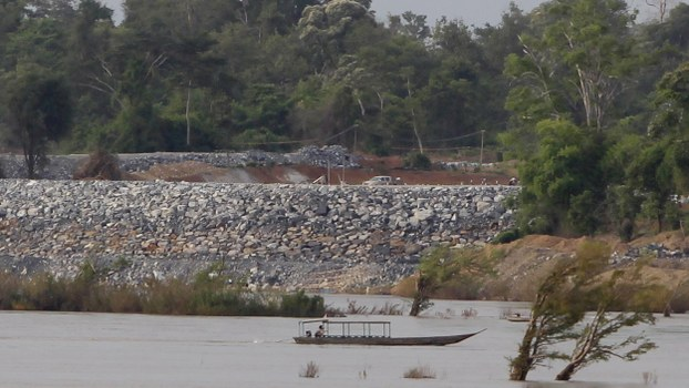 In this June 20, 2016 file photo, a fishing boat passes near a construction site of the Don Sahong dam, near Cambodia-Laos borders, in Preah Romkel village, Stung Treng province, northeast of Phnom Penh, Cambodia.