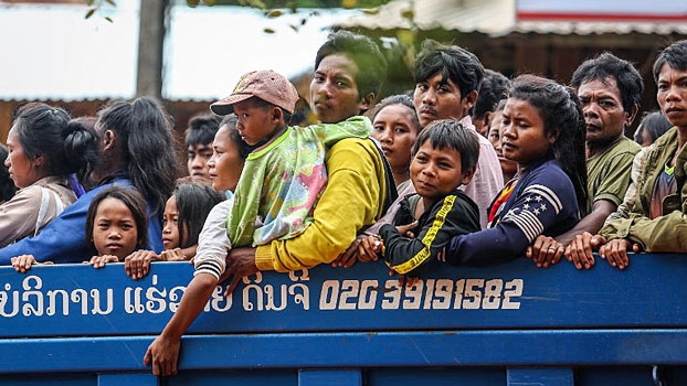 Lao villagers affected by widespread flooding caused by an auxiliary dam collapse at the Xe Pian Xe Namnoy hydropower project look out from the back of a truck as they are transported through a village in Sanamxai, southeastern Laos' Attapeu province, July 28, 2018.
