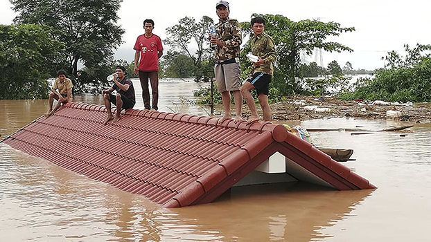 In this Tuesday, July 24, 2018, photo, villagers take refuge on a rooftop above flood waters from a collapsed dam in Attapeu province in southeastern Laos.