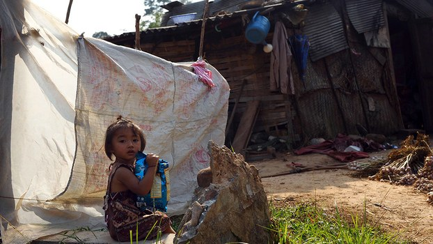 A young girl holds a bag of snacks in front of her home at a village in northern Laos' Luang Namtha province, in a file photo.