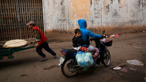 Lao woman rides with her son after shopping at a morning market in Vientiane in a file photo.