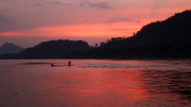 In a file photo, men ride in a boat across the Mekong river in Luang Prabang, Laos.