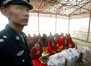 LHASA, Tibet: Chinese policeman keeps watch on crowd as Tibetan Buddhist monks chant prayers at Drepung monastery, August 2003.