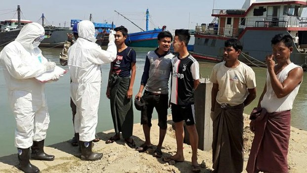 Bangladeshi health workers check Myanmar sailors who arrived at the Teknaf port for COVID-19 symptoms, March 18, 2020.