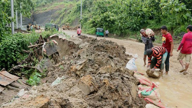 Bangladeshi volunteers attempt to curb additional landslide damage along a road in the Rangamati district, June 12, 2018.