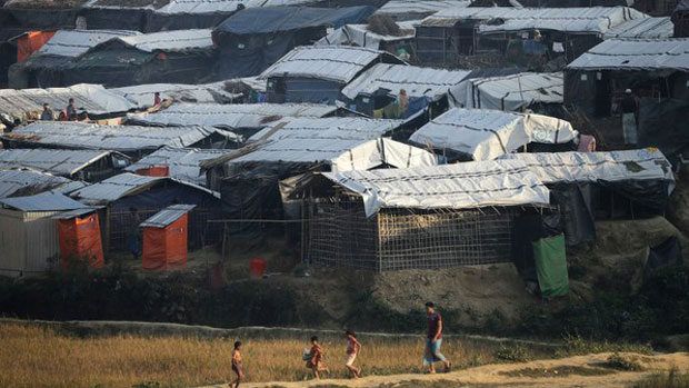 A Rohingya man and children walk through a field in the Jamtoli refugee camp in Ukhia, Bangladesh, Nov. 27, 2017.
