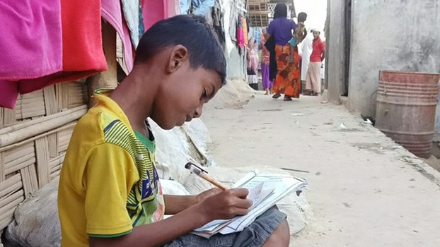 A Rohingya boy completes his school work at the Leda refugee camp in Cox's Bazar district, Bangladesh, May 16, 2020.